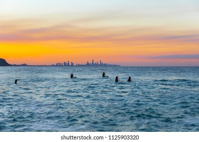 Surfers in the ocean with a colourful sunset in the skies at Surfers Paradise in the background.