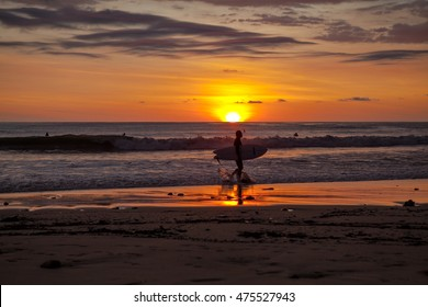 Surfers on the beach of Santa Teresa at sunset / Costa Rica