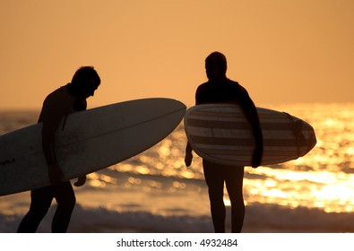Surfers on the beach at sunset