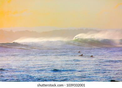 Surfers paddling out past large ocean waves at sunset