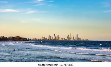 Surfers Paradise waterfront skyline with famous Q1 skyscraper from beach at Sunset. Modern cityscape beach landscape wave in Summer. Surfers Paradise city in Gold Coast region of Queensland, Australia