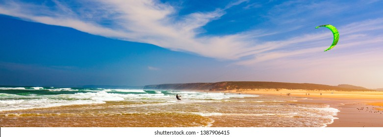 Surfers in Praia da Bordeira beach near Carrapateira, Portugal. Kiteboarder kitesurfer athlete performing kitesurfing kiteboarding tricks. Praia da Bordeira is popular location for surfing. Portugal