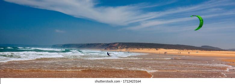 Surfers in Praia da Bordeira beach near Carrapateira, Portugal. Kiteboarder kitesurfer athlete performing kitesurfing kiteboarding tricks. Praia da Bordeira is popular location for surfing. Portugal
