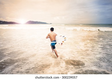 surfers running into the sea with surf boards on patong puket thailand,vintage Instagram retro hipster