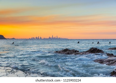 Surfers sitting in the ocean surf with a colourful sunset in the sky at Currumbin Gold Coast