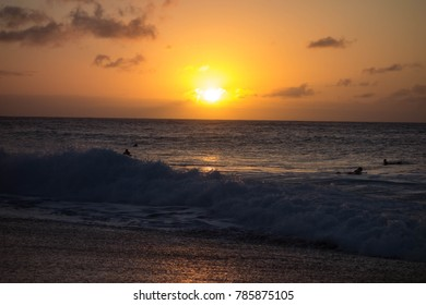Surfers at sunset at Bansai Pipleine at the North Shore in Oahu, Hawaii.