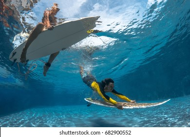 Surfers with surf board dive underwater with fun