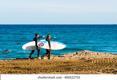 surfers walking along the beach