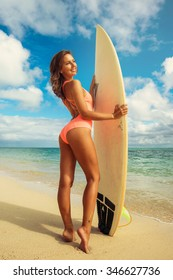 Surfgirl posing. Beautiful young surfgirl go surfing in the clear waves. She rides in the Indian Ocean island of Mauritius