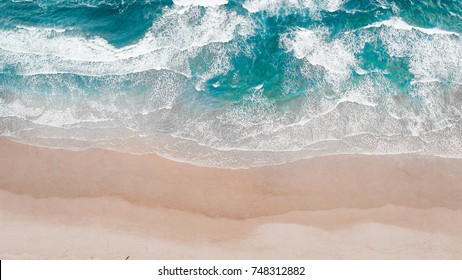 Surfing Aerial, Beach on aerial drone top view with ocean waves reaching shore, top view aerial photo from flying drone of an amazingly beautiful sea landscape.