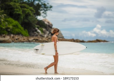 Surfing beach woman. Happy surfer girl running laughing cheerful having fun with bodyboarding surfboard on summer holidays vacation travel on Tropical ocean beach