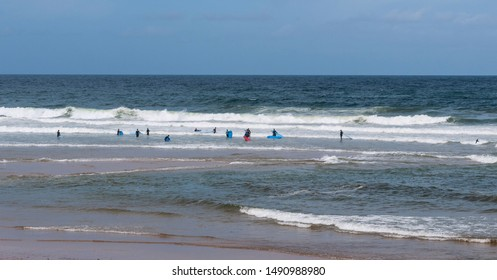 A surfing class in the ocean, taken from a beach in Portugal.