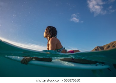 Surfing girl waiting for a wave incoming lying on a surf board. Shoot splitted by water line with blue sky on a background