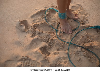 Surfing leash on female leg close up, surfing concept.