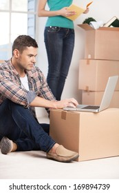 Surfing the net in a brand new house. Confident young man sitting on the floor and working on laptop while woman unpacking a carton box on the background