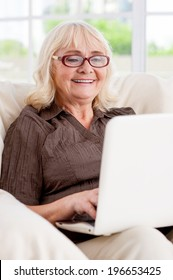 Surfing the net is fun. Senior woman working on laptop and smiling while sitting at the chair
