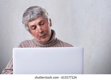Surfing the net at home. Pensive mature man wearing eyeglasses and casual sweater reading a book on his laptop while siting at home having dreaming expression. People, age, leisure concept.