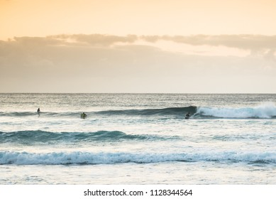Surfing on volcano beach. Surfer catching waves.