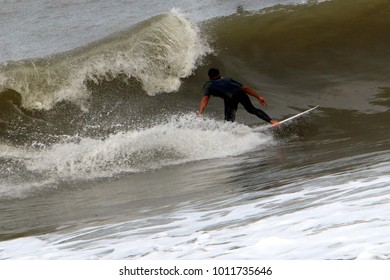 Surfing - riding athletes on a wave on special light boards.