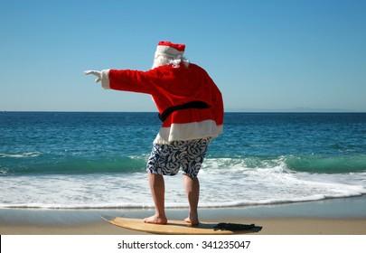 Surfing Santa. Santa Claus Surfs on his Surf Board while on a Beautiful Beach with a Blue Ocean. Focus on Santa/s Face. Santa Vacation. Surfing Santa. Santa goes Surfing.