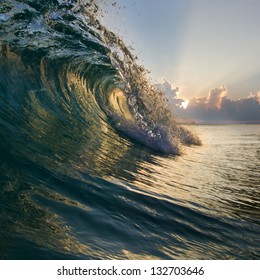 Surfing tropical design template. Breaking curled shorebreak wave with beautiful sunset