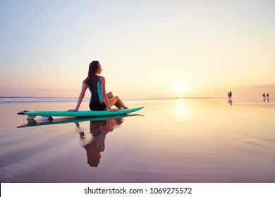 Surfing and vacation. Holiday on the beach. Relaxed young woman siiting on the sand with surf board enjoying sunset.