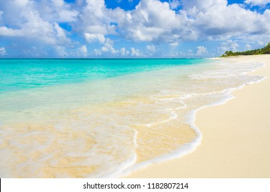 Surfs edge on white sand beach at Shoal Bay in Anguilla.