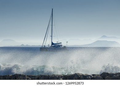 surge at a rocky beach with sailboat and mountains of an island in haze, concept for travel, watersports and vacation, Lanzarote, canary islands, Spain, Europe