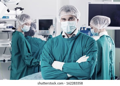 Surgeon with arms crossed looking at camera with colleagues performing in background