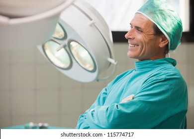 Surgeon being happy while sitting in a operating room with crossed arms