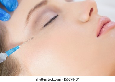 Surgeon in bright operating room making injection on woman's crows feet