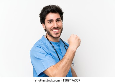 Surgeon doctor man over isolated white wall celebrating a victory