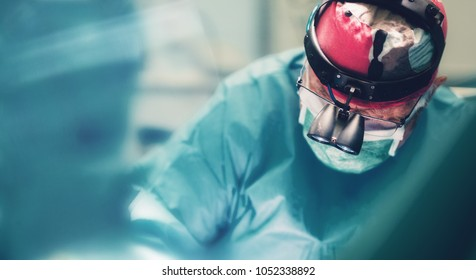Surgeon doctor operating using special lamp lighting and glasses loupes wearing blue surgical mask and surgical cap in surgery room with his team  surgeons operating
