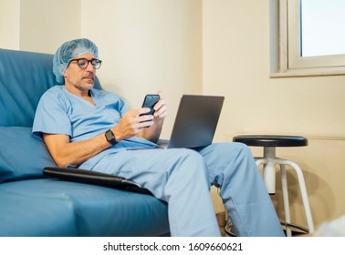 The surgeon doctor using laptop and mobile phone after operation