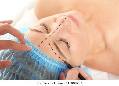 Surgeon hands drawing marks on female face for plastic operation