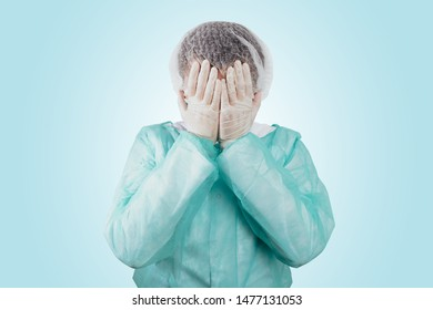 The surgeon holds his head after surgery wearing a green surgical apron and a face mask on a light background. Medical and pharmaceutical concept. Failure of surgery, sadness, medical errors.
