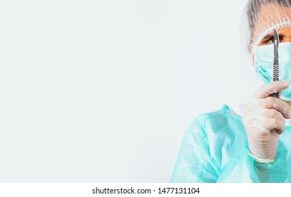 Surgeon holds scalpel dressed in a green surgical apron and mask on light background. Medical and pharmaceutical concept. Scalpel surgeon's scissors, just before surgery. Responsible work of surgeon.