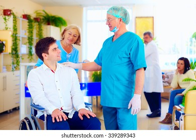 surgeon and medical staff talking with young adult man in wheelchair, in hospital