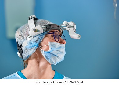 Surgeon performing surgery in hospital operating room. Surgeon in mask wearing loupes during medical procadure.