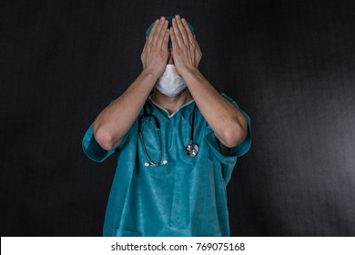 Surgeon in scrubs covering eyes. Black background