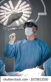 Surgeon using augmented reality holographic hololens glasses, preparing for liver tumor operation