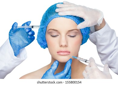 Surgeons making injection on calm blonde on white background