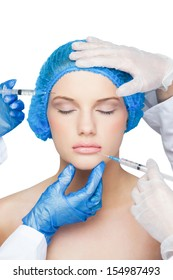 Surgeons making injection on peaceful blonde on white background