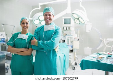 Surgeons standing up while smiling in an operating theatre