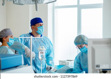 Surgeons team preforming operation in hospital operating theater, male surgeon operating patient,wearing surgical gown,operating room,,working with surgical laparoscopy instruments. Gynecology.