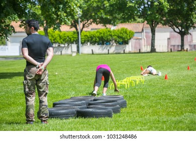 Surgeres, France - June 19, 2016 : Fit young woman jumping on tire at a crossfit style outdoor gym while coach watching woman at Surgeres, France.