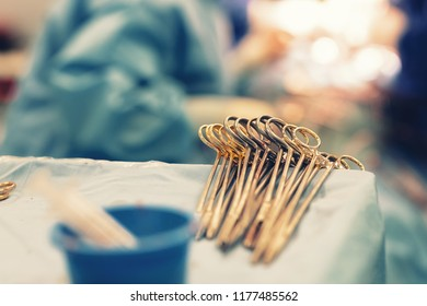 Surgery instruments on table covered by sterile field in surgery operation room with team surgeons in surgery center for interventions with instruments for microsurgery