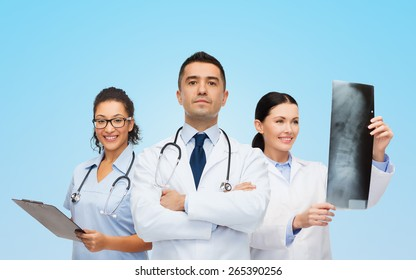 surgery, profession, people and medicine concept - group of medics with x-ray over blue background