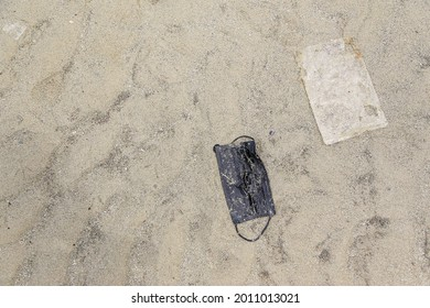 Surgical face mask and plastic bag leave as garbage on sea sand. Concept of environmental pollution impact form coronavirus covid 19 pandemic.