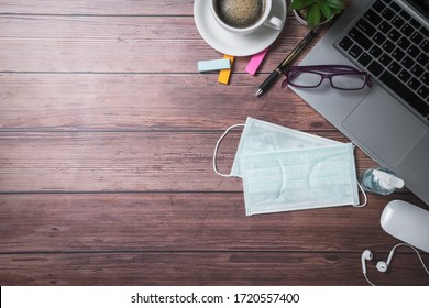 surgical face mask and sanitizer bottle or alcohol gel with laptop and  coffee on old wood background, work from home and covid-19 and new normal concept